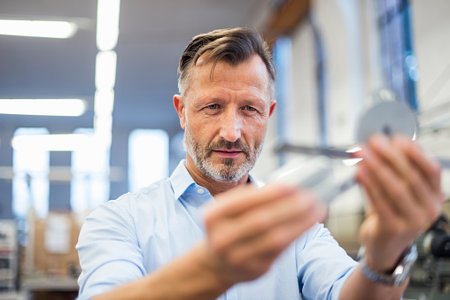 Mature businessman in factory examining component - gettyimageskorea
