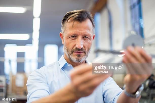 mature businessman in factory examining component - ingenieur stock-fotos und bilder