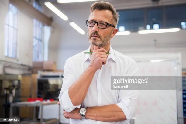 mature businessman in factory thinking - beschaulichkeit stock-fotos und bilder