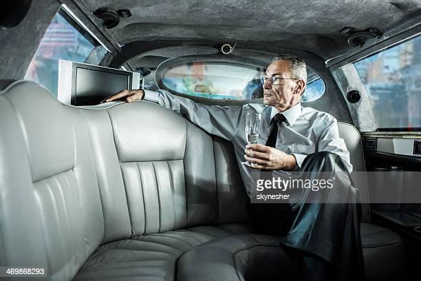 Reifer Geschäftsmann in einer limousine.