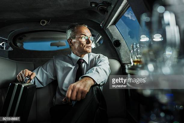 Mature businessman in limousine.