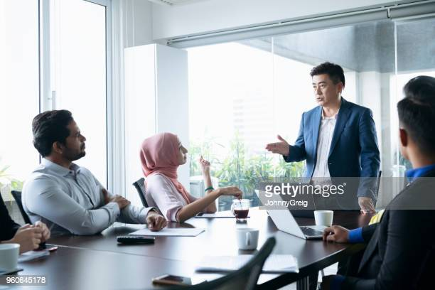 mature businessman in meeting with colleagues - instructions stock pictures, royalty-free photos & images