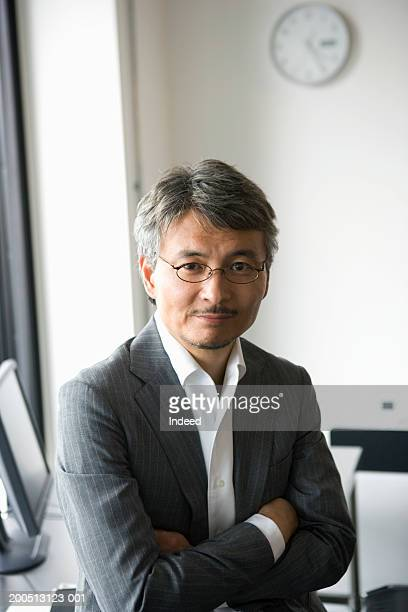 Mature businessman in office, arms folded, portrait