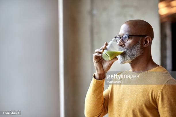 mature businessman in office drinking a smoothie - healthy stock pictures, royalty-free photos & images