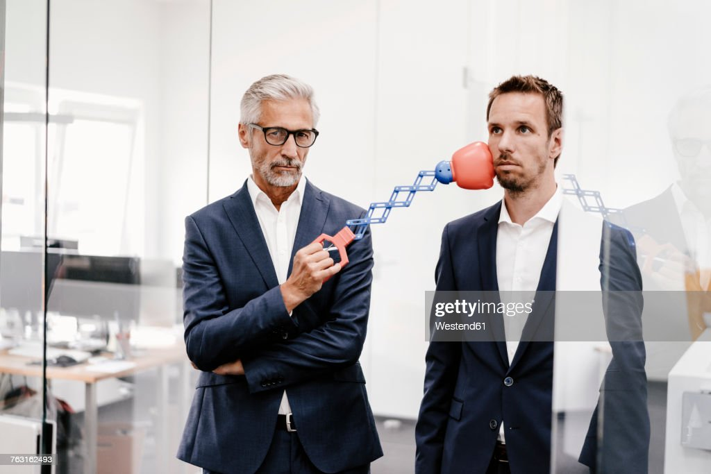 Mature businessman in office hitting colleague with boxing toy : Stock Photo