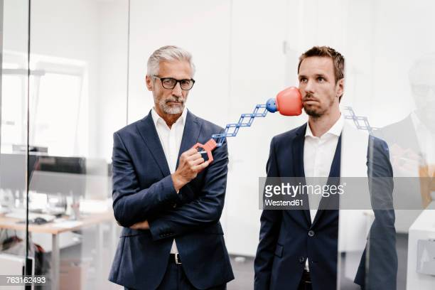 mature businessman in office hitting colleague with boxing toy - konflikt stock-fotos und bilder