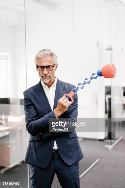 Mature businessman in office holding boxing toy