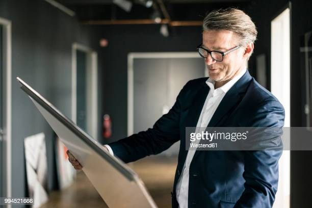 mature businessman in office looking at painting - art dealer stock pictures, royalty-free photos & images