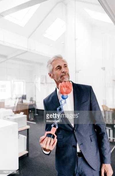 Mature businessman in office receiving an uppercut