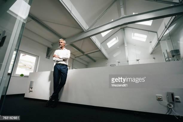 mature businessman in office thinking - weitwinkel stock-fotos und bilder