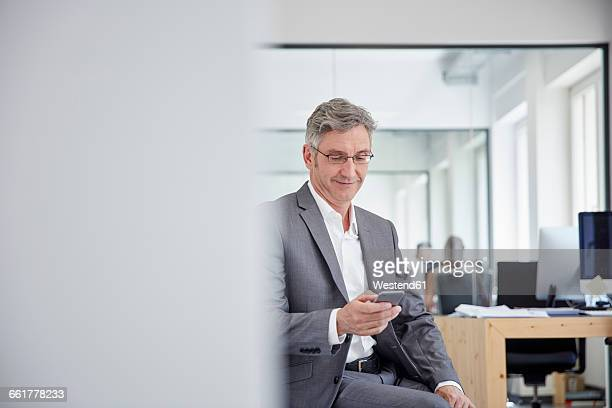 Mature businessman in office using smart phone