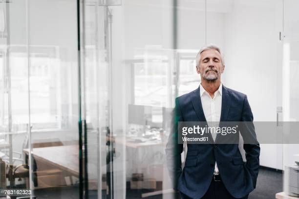 mature businessman in office with closed eyes - gelassene person stock-fotos und bilder