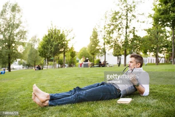 mature businessman in the city park lying on grass - sdraiato foto e immagini stock