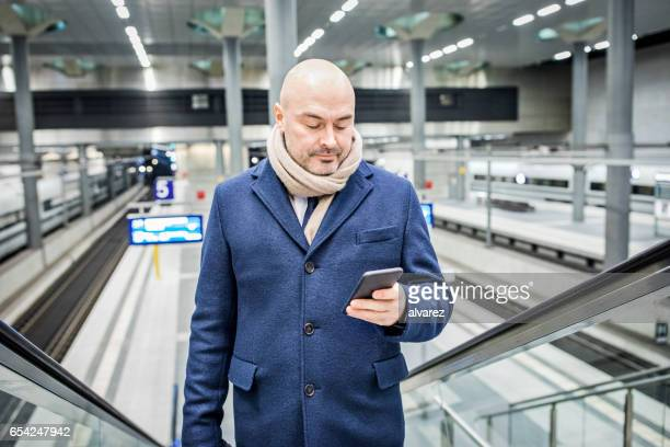 Mature businessman in the metro station using mobile phone
