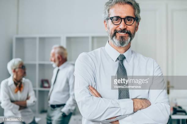 reifer geschäftsmann im büro. - arbeitende rentner stock-fotos und bilder