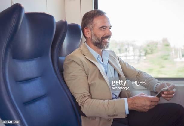 mature businessman in train - solo un uomo maturo foto e immagini stock
