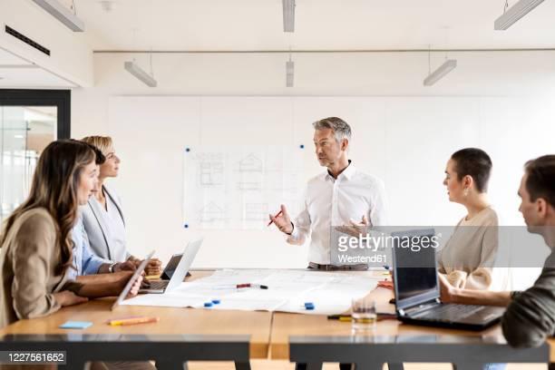 mature businessman leading a meeting in office - mitarbeiterengagement stock-fotos und bilder