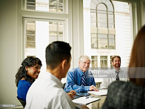 Mature businessman leading coworkers in discussion