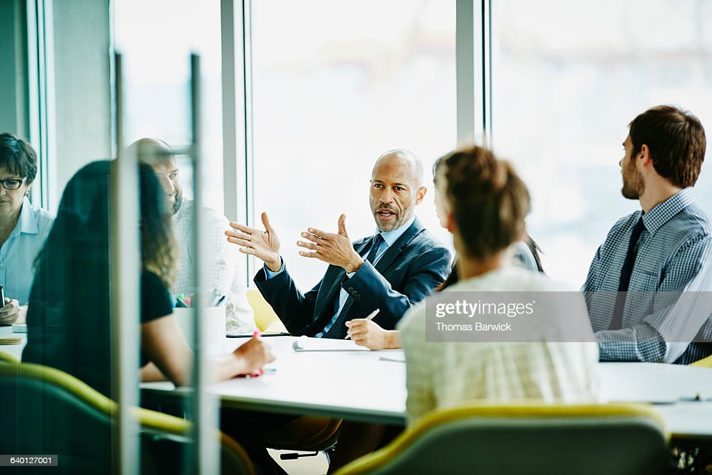 Mature businessman leading meeting in office : Stock Photo