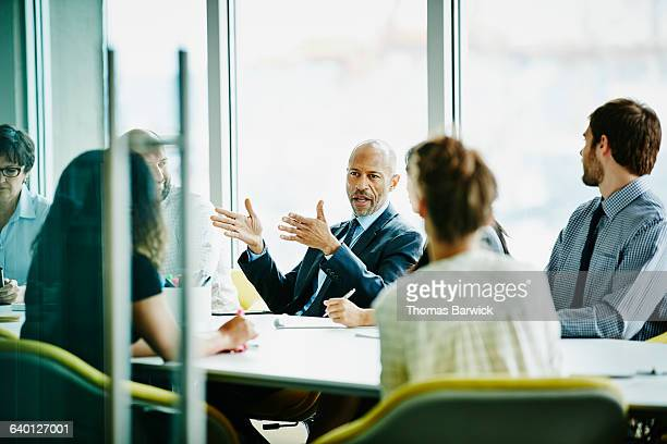 mature businessman leading meeting in office - tavolo da conferenza foto e immagini stock