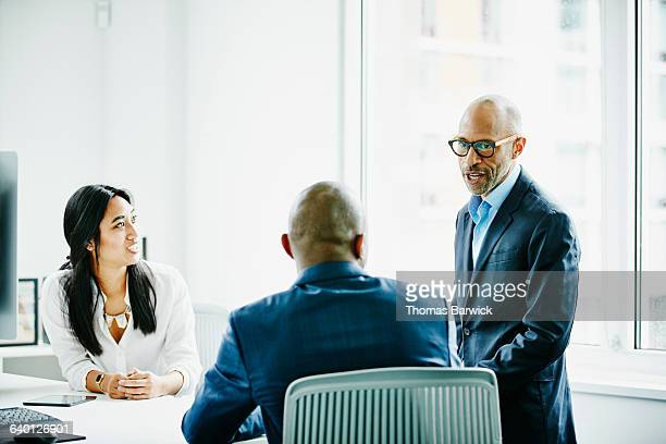Mature businessman leading meeting with colleagues