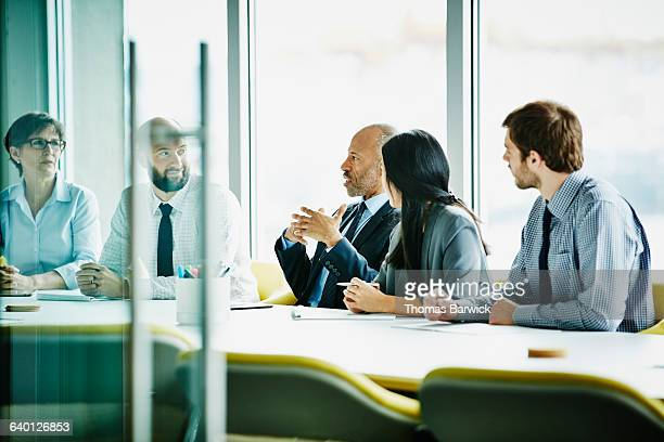 Mature businessman leading team in office