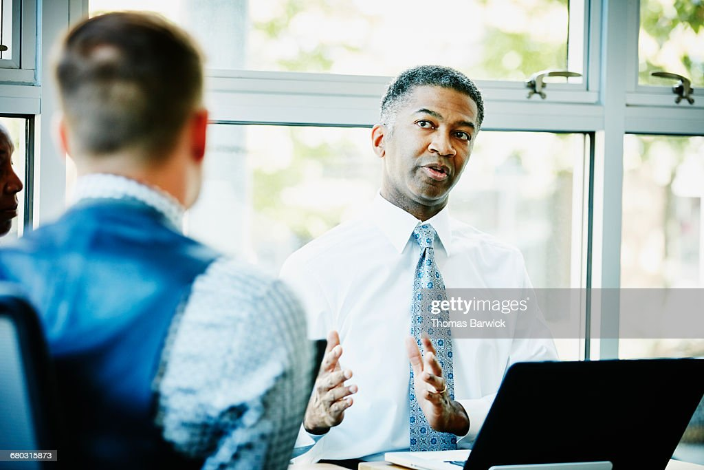Mature businessman leading team meeting in office : Stock Photo