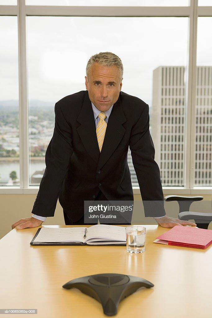 Mature businessman leaning on desk, smiling, portrait : Foto stock