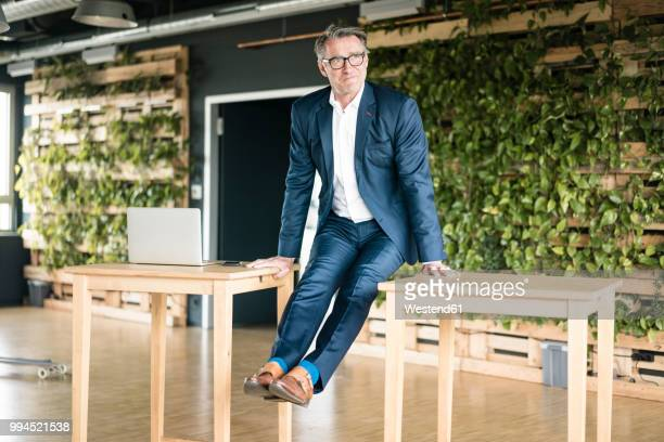 mature businessman leaning on tables in green office - green suit stock pictures, royalty-free photos & images