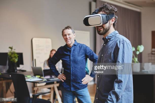 mature businessman looking at male colleague using virtual reality simulator while standing in creative office - virtual reality simulator stock photos and pictures