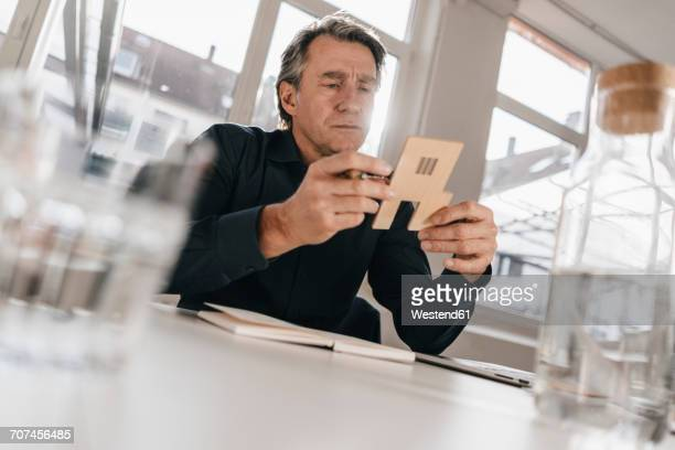 Mature businessman looking at model in office