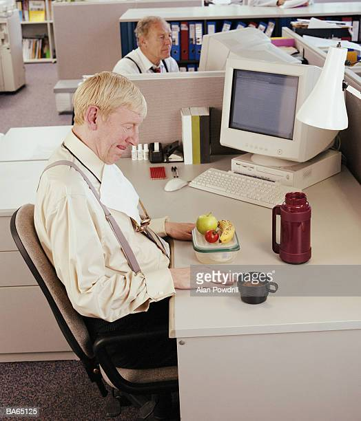 Mature businessman looking at packed lunch on desk