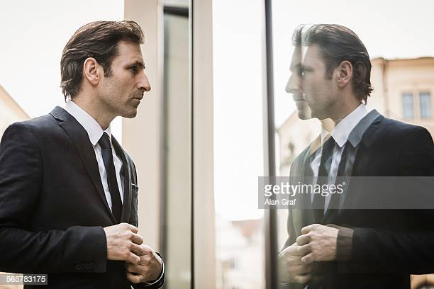 Mature businessman, looking at reflection in window