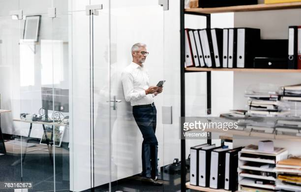Mature businessman looking at tablet in office