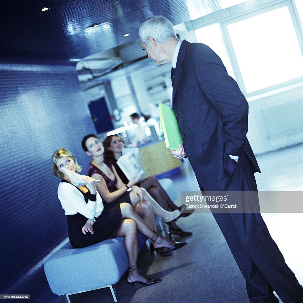 Mature businessman looking at three young women. : Stock-Foto