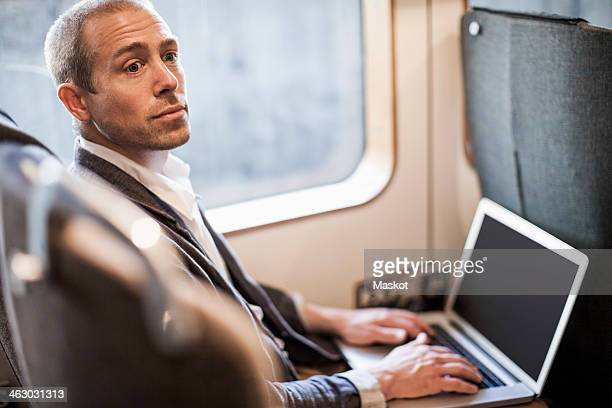 Mature businessman looking away while using laptop in train
