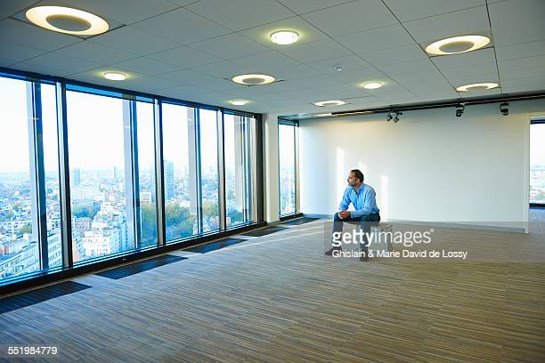 Mature businessman looking from empty office window at Brussels cityscape, Belgium