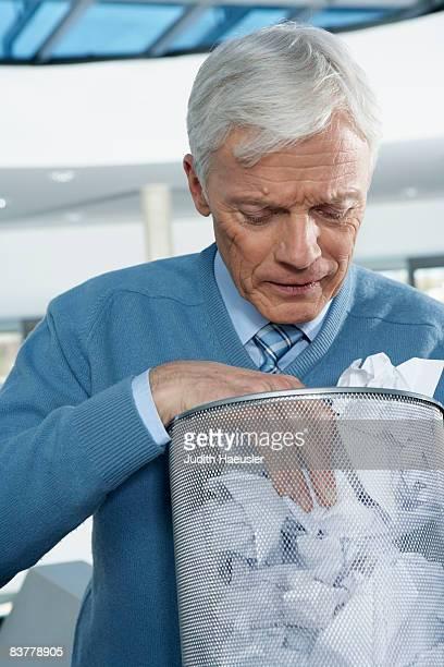 Mature businessman looking into bin