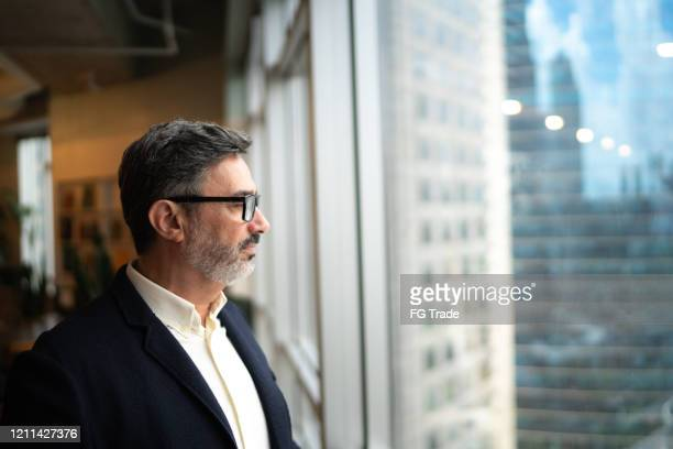 mature businessman looking out of window - gratitude stock pictures, royalty-free photos & images