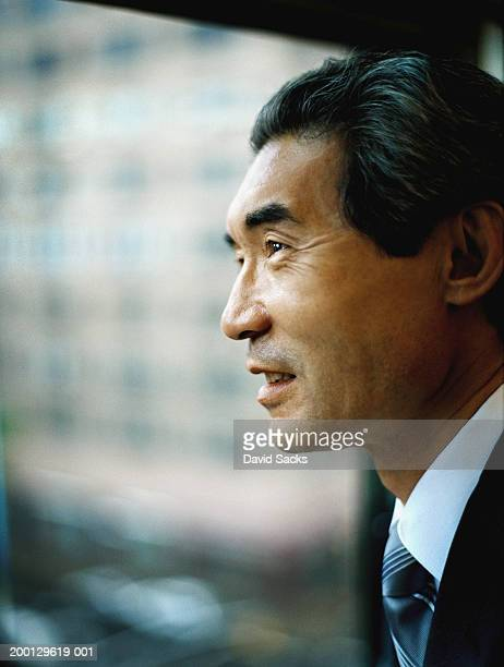 Mature businessman looking out of window, side view, close up
