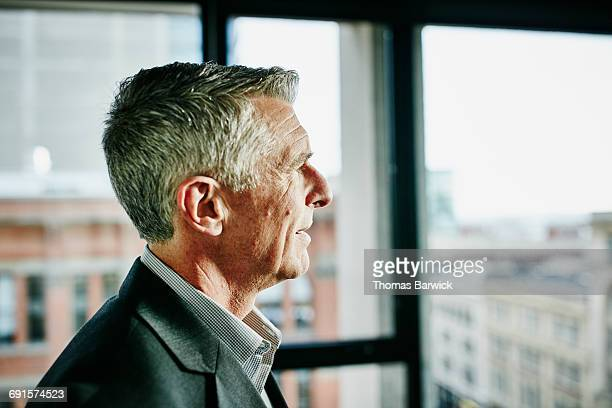 Mature businessman looking out office window