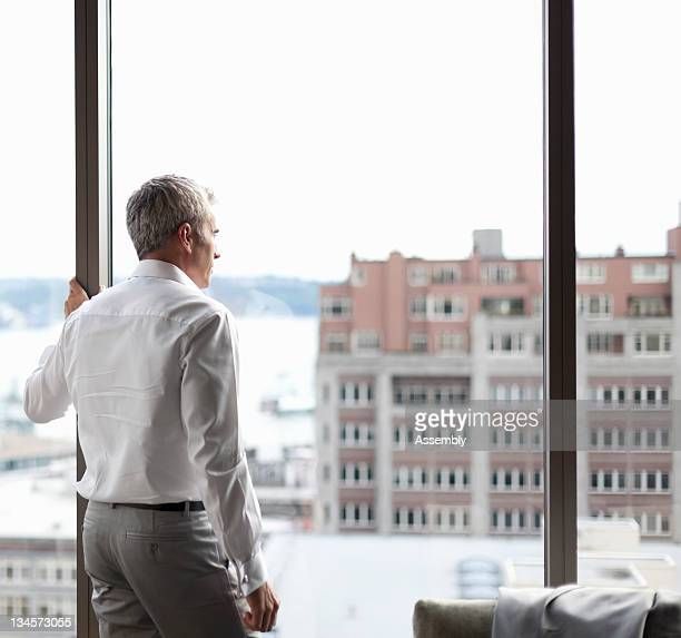 Mature businessman looking out window.