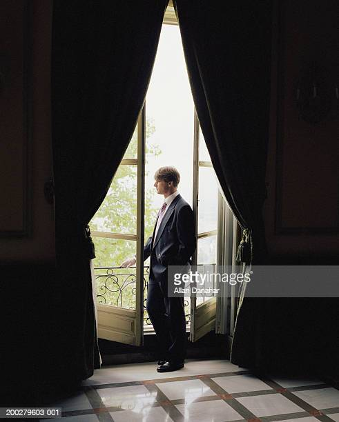 Mature businessman looking out window, view from indoors