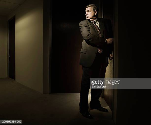 mature businessman looking over shoulder while closing office door - looking over shoulder ストックフォトと画像
