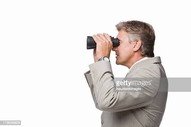 Mature businessman looking through binoculars