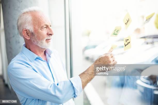 Reife Geschäftsmann ganze Fenster suchen und halten gelben Aufkleber