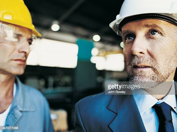 Mature Businessman Looking Up and Standing by a Factory Worker in a Factory