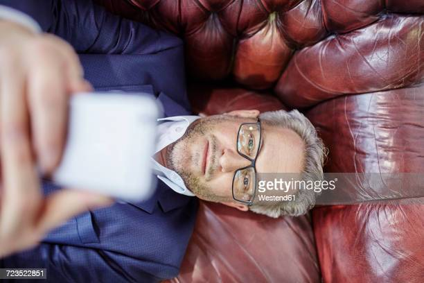 mature businessman lying down looking on cell phone - lying down stock-fotos und bilder