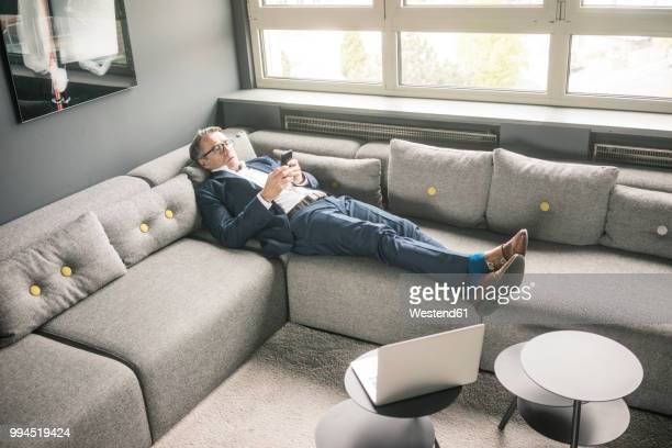 mature businessman lying on couch using cell phone - convenience stock photos and pictures