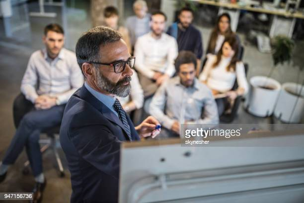mature businessman making a plan for his colleagues on a training class. - presenter stock pictures, royalty-free photos & images